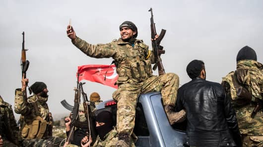 A Syrian opposition fighter takes a selfie as fighters walk through Syria in front of Turkish troops near the Syrian border at Hassa, Hatay province, on January 22, 2018.