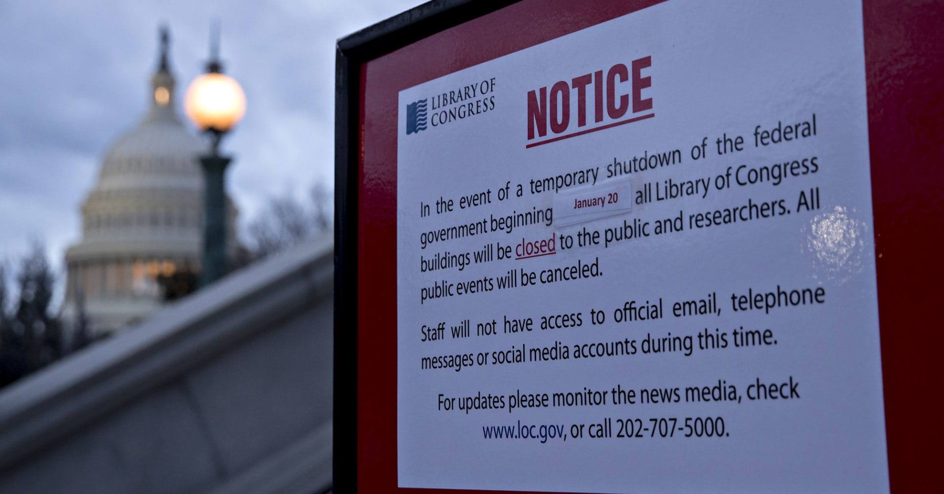 The U.S. Capitol stands past a temporary shutdown sign outside the Library of Congress in Washington, D.C., U.S., on Sunday, Jan. 21, 2018.
