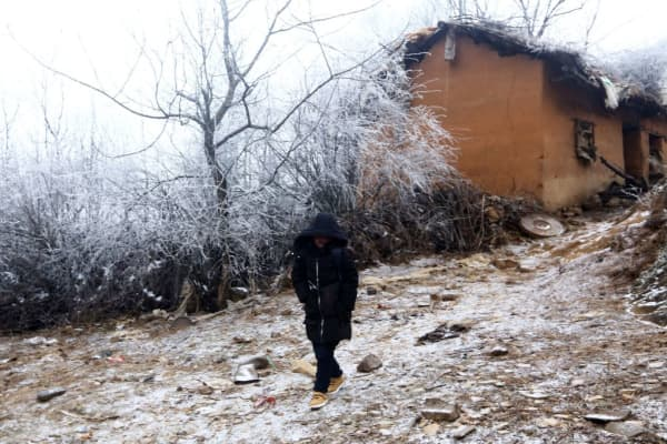 Wang Fuman, also known as 'Frost Boy', walks on the road in Ludian in China's southwestern Yunnan province on January 12, 2018.