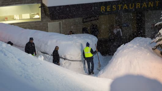 Patrons arrive at a restaurant through high snow banks in Davos, Switzerland.