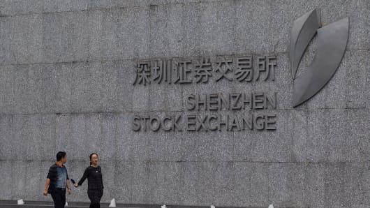 People walk past Shenzhen Stock Exchange building on March 9, 2016 in Shenzhen, China.