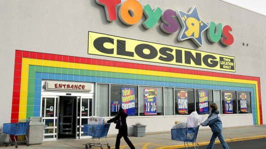 Pers Push Their Carts Toward A Toys R Us With Closing Sign