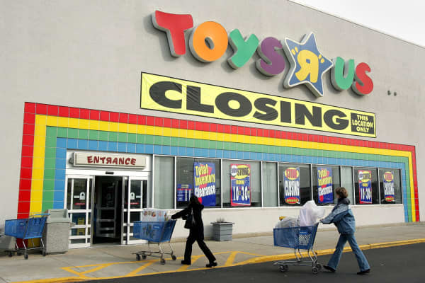 Shoppers push their carts toward a Toys R Us store with a closing sign.