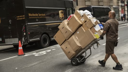 United Parcel Service (UPS) driver pushes a dolly of packages towards a delivery van on a street in New York.
