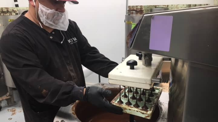Kiva Confections worker creating a cannabis infused chocolate bar at the company's factory