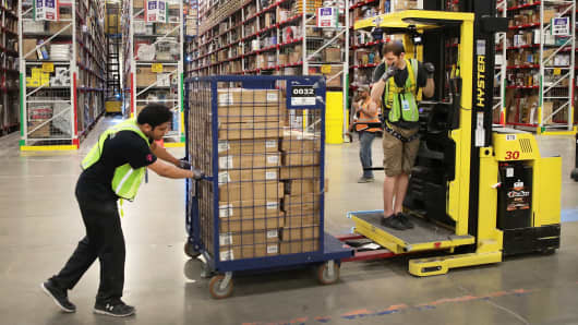 Workers pack and ship customer orders at the 750,000-square-foot Amazon fulfillment center in Romeoville, Illinois.