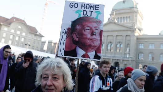 A woman holds a sign with a portrait of the US president during a protest against his planned visit to the World Economic Forum in Davos, in Bern on January 13, 2018.