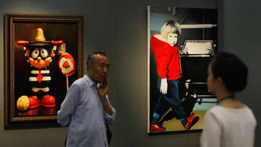 Visitors view artwork during the 2012 Poly Spring Auction Exhibition in Beijing, China.