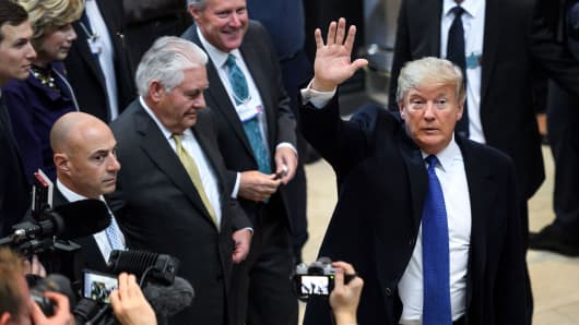 President Donald Trump (R) waves upon his arrival with Secretary of State Rex Tillerson (2ndL) for the World Economic Forum (WEF) annual meeting in Davos, eastern Switzerland, on January 25, 2018.