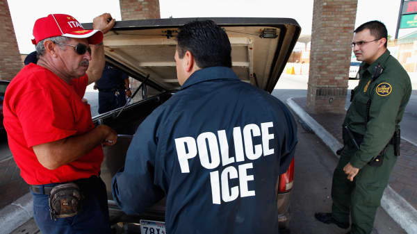 Special agents from Immigration and Customs Enforcement (ICE) question a man while his vehicle is searched after he was stopped heading into Mexico at the Hidalgo border crossing.