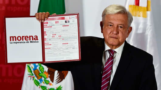 The president of the National Regeneration Movement (MORENA), Andres Manuel Lopez Obrador, shows the document after registering himself as a pre-candidate for Mexico's presidential election in July, in Mexico City, on December 12, 2017.