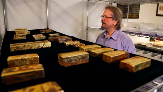 Chief scientist Bob Evans looks at gold bars recovered from the S.S. Central America steamship that went down in a hurricane in 1857 in a laboratory Tuesday, Jan. 23, 2018, in Santa Ana, Calif. More than $50 million worth of gold bars, coins and dust described as the greatest lost treasure in U.S. history is about to make its public debut in California.