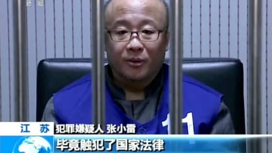 In this image taken from undated video footage run by China's CCTV via AP Video, Qianbao founder Zhang Xiaolei speaks with police while in custody in Nanjing in eastern China's Jiangsu province.
