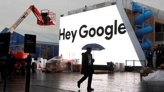 A man walks through light rain in front of the Hey Google booth under construction at the Las Vegas Convention Center in preparation for the 2018 CES in Las Vegas, Nevada, January 8, 2018.