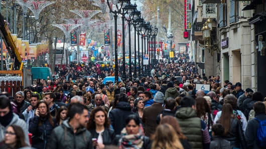 People walk along a crowed shopping street on the first day of the winter sales on January 7, 2015 in Barcelona, Spain