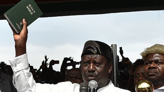 Kenya's opposition National Super Alliance (NASA) coalition leader Raila Odinga holds up a bible as he swears-in himself as the 'people's president' on January 30, 2018, in Nairobi.