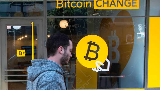 A pedestrian walks past the cryptocurrency 'Bitcoin Change' shop.