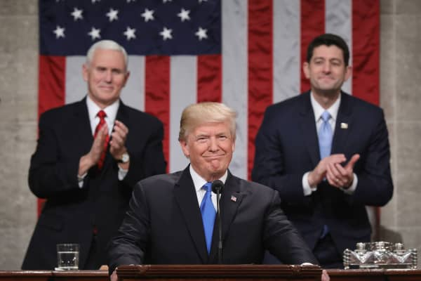 President Donald J. Trump (C) stands at the podium as U.S. Vice President Mike Pence (L) and Speaker of the House U.S. Rep. Paul Ryan (R-WI) (R) look on during the State of the Union address in the chamber of the U.S. House of Representatives January 30, 2018 in Washington, DC.