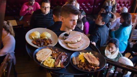 A waiter carries a tray of food to patrons at the Bayside American Cafe in Portland, Oregon.