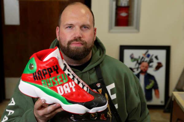 Mache Custom Kicks founder Dan Gamache holds a shoe he painted for WWE wrestler Miroslav Barnyashev, better known by his ring name, Rusev.