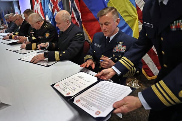 U.S. Coast Guard Commandant Adm. Paul Zukunft, holding pen, joins leaders in signing a joint statement adopting doctrine, tactics, procedures and information-sharing protocols for emergency maritime response in the Arctic in Boston on March 24, 2017.
