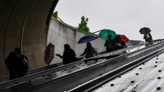 Metro commuters use the escalator at the Dupont Circle Metro station during a light rain in Washington, D.C.