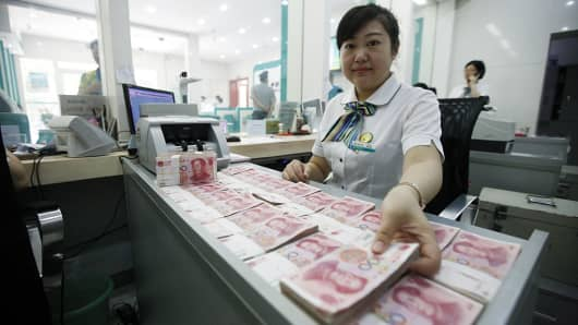 A Worker Counts Chinese Currency Renminbi At Bank In China