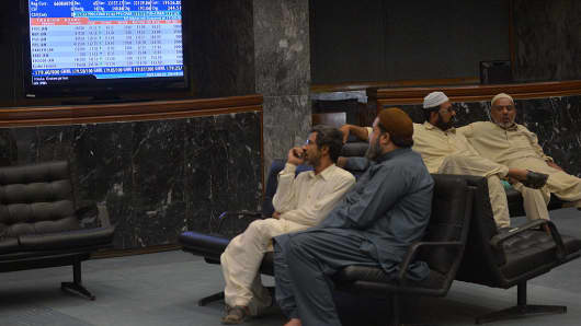 Pakistani stockbrokers monitor share prices during a trading session at the Karachi Stock Exchange on January 1, 2016.