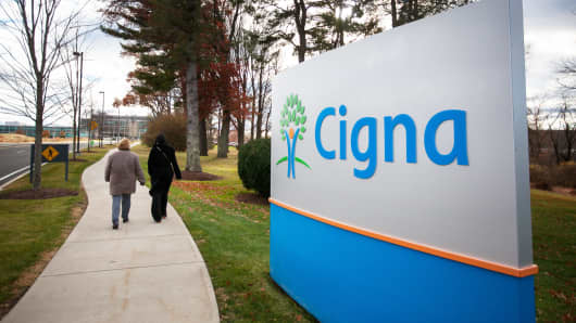 Pedestrians walk passed signage at Cigna headquarters in Bloomfield, Connecticut.
