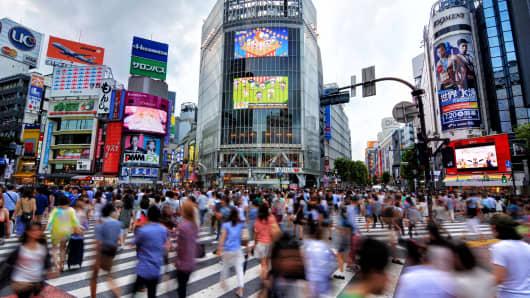 Motion blur of busy pedestrians walking at famous Shibuya Crossing, Tokyo, Japan