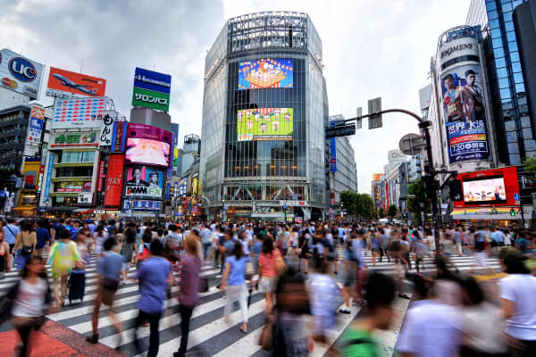 Motion blur of busy pedestrians walking at famous Shibuya Crossing, Tokyo, Japan