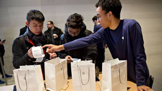 An employee assists a customer who purchased four Apple Inc. iPhone X smartphones during the sales launch at a store in Chicago.