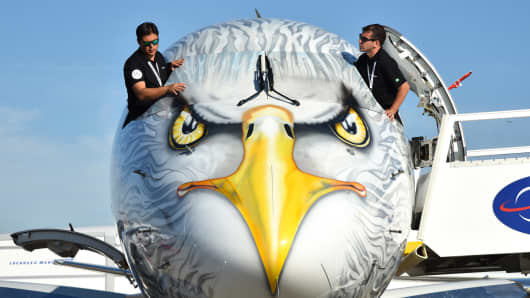 Crew members cover windows of Embraer E190-E2 during the 52nd International Paris Air Show at the Le Bourget Airport near Paris, France on June 20, 2017.