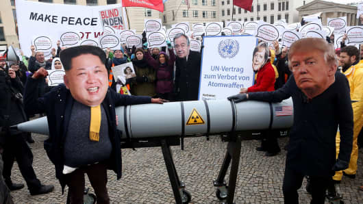 An activist with a mask of Kim Jong-un, chairman of the Workers' Party of Korea and supreme leader of North Korea (L), and another with a mask of U.S. President Donald Trump, march with a model of a nuclear rocket during a demonstration against nuclear weapons on November 18, 2017 in Berlin, Germany.