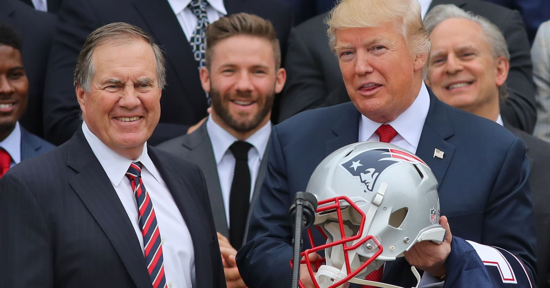 President Donald Trump holds a New England Patriots helmet as Patriots head coach Bill Belichick, left, and Patriots player Julian Edelman, rear, look on during a ceremony at the White House in Washington D.C. on Apr. 19,. 2017.