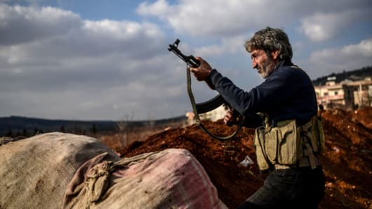 A Turkish-backed Syrian rebel fighter stands guard at a checkpoint in the Syrian town of Azaz on a road leading to Afrin, on February 1, 2018. Clashes raged between Turkish-backed forces and Kurdish militia in Syria's Afrin region on January 31, 2018, as wounded civilians fled intense Turkish air strikes. Turkey and allied Syrian rebels have pressed on with Operation Olive Branch in the Kurdish-controlled Afrin enclave despite mounting international concern and reports of rising civilian casualties.