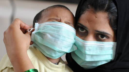 An Indian mother and son wear masks as they stand in a queue at The Government Chest Hospital in Hyderabad on August 11, 2009.