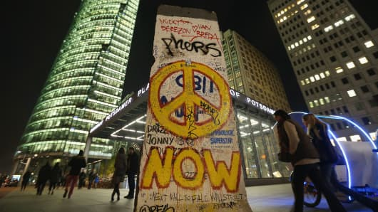 People walk past an original graffiti-covered portion of the Berlin Wall at a spot where the outer layer of the Wall once stood at Potsdamer Platz on October 29, 2014 in Berlin, Germany.