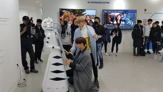 "Members of the popular Korean pop group ""Seventeen"" interact with a Furo-D robot at the ICT Pavilion in PyeongChang on January 31, 2018. South Korean robotics company Future Robot will be providing 30 Furo-D robots during the PyeongChang Games, which will act as guides and translators across the arenas and airport."