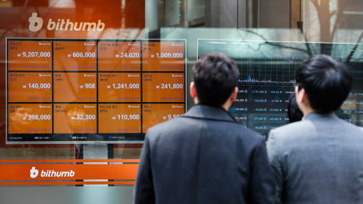 Pedestrians look at monitors showing the prices of virtual currencies at the Bithumb exchange office in Seoul, South Korea, Feb. 2, 2018.