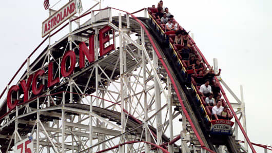 Visitors to Coney Island enjoy a thrill ride on the world famous 'Cyclone' rollercoaster