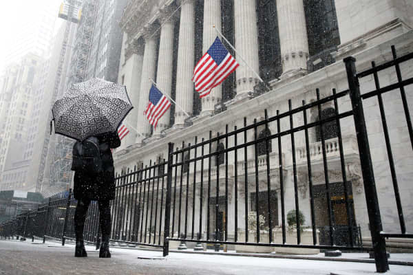 A woman looks up as snow begins to fall in front of the New York Stock Exchange, (NYSE) during the morning commute in New York City, U.S., February 7, 2018.