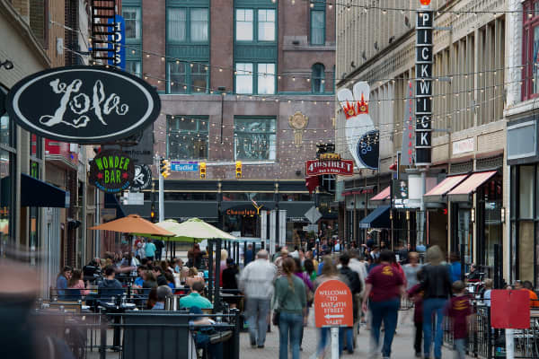 Pedestrians walk past restaurants and shops on East 4th Street in downtown Cleveland, Ohio, U.S.