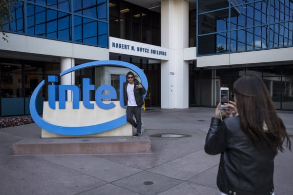A man poses for a photograph in front of Intel Corp. signage in front of the company's headquarters in Santa Clara, California, U.S., on Monday, Oct. 17, 2016.