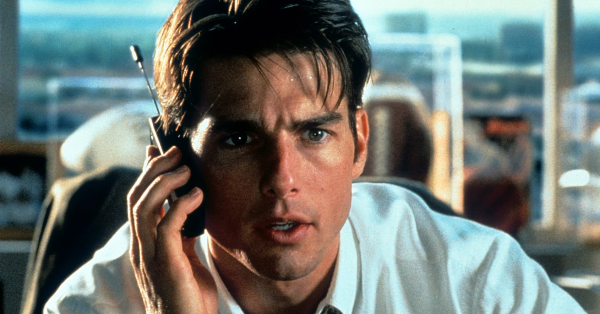 Tom Cruise talks on a phone in a scene from 'Jerry Maguire,' a film in which his character is fired from a job at a sports management agency.
