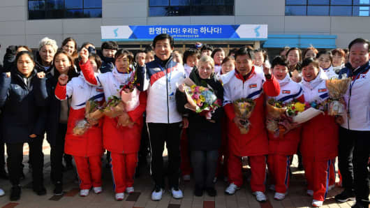 Sarah Murray (C), head coach of the two Korea's unified women's ice hockey team , Pak Chol-Ho (4th R) head coach of the North Korean women's ice hockey team and South and North Korean players cheer during a welcoming ceremony after arrive at South Korea's national training center on January 25, 2018 in Jincheon, South Korea.
