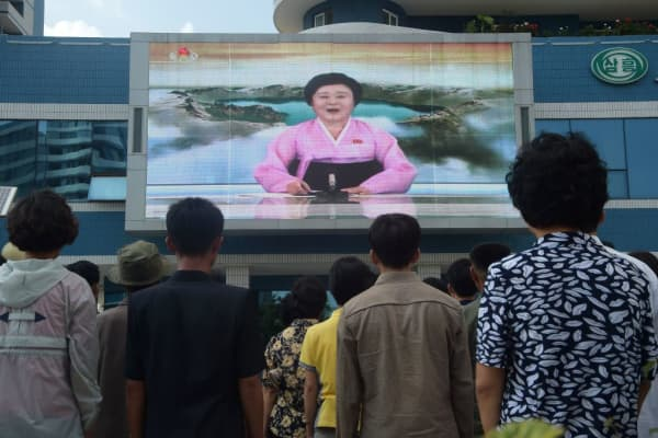 Residents watch a big video screen on Mirae Scientists Street in Pyongyang showing newsreader Ri Chun-Hee as she announces the news that the country has successfully tested a hydrogen bomb on September 3, 2017.