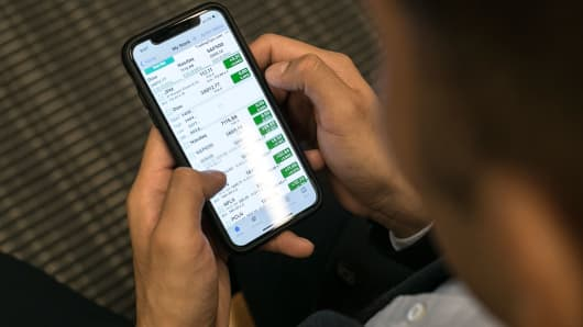 Mario Tehuitzil, a medical student at New York University, checks his stocks on a phone in New York, Feb. 7, 2018.