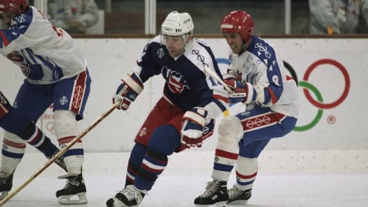 U.S. hockey player David Emma of Cranston, R.I., is chased by France's Patrick Dunn during their quarterfinal game in Meribel, Tuesday, Feb. 18, 1992 in France.
