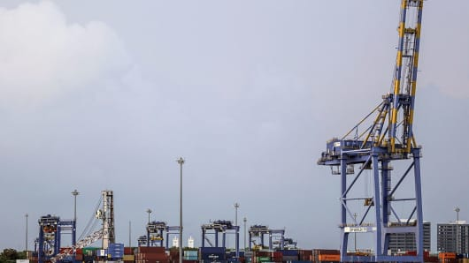 Shipping containers and gantry cranes stand at a container transhipment terminal operated by DP World in Cochin, India.